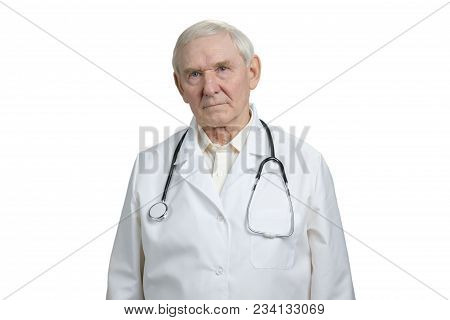 Old Serious Gloomy Doctor Portrait. Senior Physician With Stethoscope In White Isolated Background.