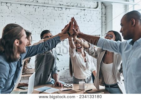 High-five For Success! Diverse Group Of Business Colleagues Giving Each Other High-five In A Symbol