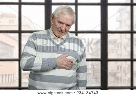 Senior Grandfather Feeling Heart Pain. Checkered Windows Background With View On City.