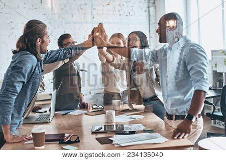 High-five! Group Of Business Colleagues Giving Each Other High-five While Working Behind The Glass W