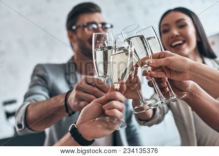 Colleagues And Friends. Group Of Young Business People Toasting Each Other And Smiling While Standin