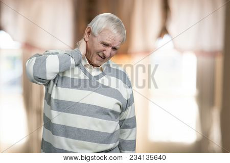 Old Man Has Neck Pain. Senior Suffers From Neckache Indoor At Home.