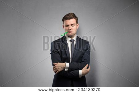 Young tired businessman with thermometer and copy space