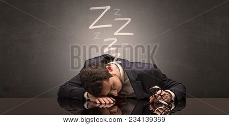 Young businessman fell asleep at the table concept