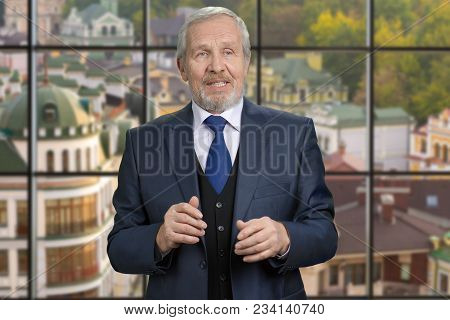 Old European Politician Man Portrait. Senior Man In Suit Talking, Checkered Windows Background With