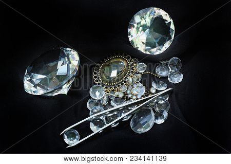 Sparkling Diamonds Pile On Black Background With Tweezers Holding One For Authentication