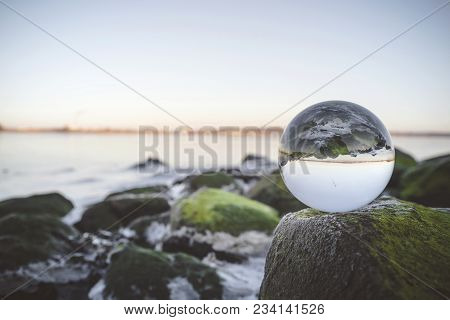 Glass Orb On Rocks By The Sea Covered With Green Moss