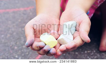 Chalk In Child's Hands Close-up. The Child Drawing A Chalk On Asphalt. Child Drawings Paintings On A