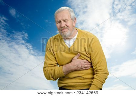 Old Man Having Heart Attack. Suffering From Heart Pain Against Blue Cloudy Sky Background.