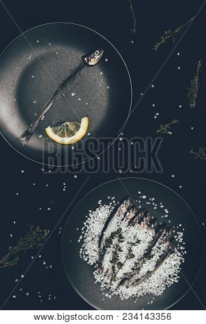 Frying Pan With Skeleton Of Fish With Lemon Slice And Other Frying Pan With Salted Pile Of Fish Surr