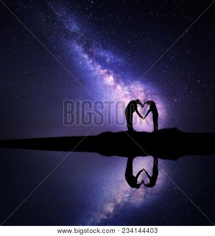 Milky Way. Night Landscape With Starry Sky And Man And Woman Holding Hands In Heart Shape On The Mou