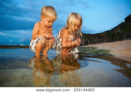 Happy Sibling Children Have Fun On Sunset Sand Beach, Exploring Underwater World In Water Pool At Se