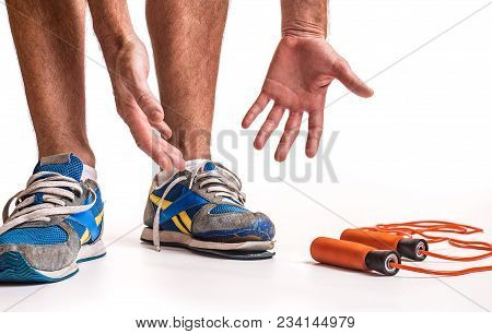 Man Looking Down In Frustration At His Worn Out Pair Of Training Shoes.