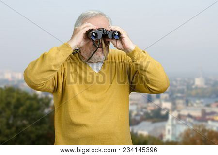Old Man Looking Through Binocular On The City View. Senior Tourist Observing City Locations Using Bi
