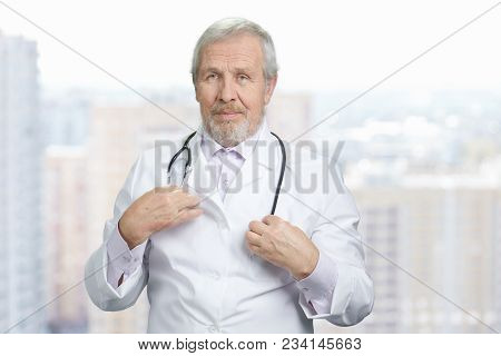 Portrait Of Doctor Touching Stethoscope. Medical Equipment Rearranging. City Skyscrappers Background