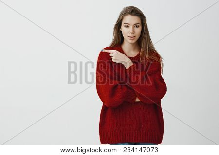 Good-looking Caucasian Female Coworker In Trendy Red Loose Sweater, Pointing Left With Index Finger,