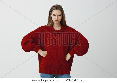 Studio Portrait Of Displased Angry Caucasian Girlfriend In Red Loose Sweater, Holding Hands On Hips