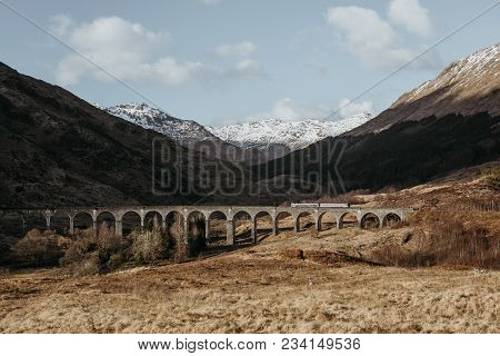 View Of Glenfinnan Viaduct With A White Train Passing Across, Glenfinnan, Scotland, On A Sunny Sprin
