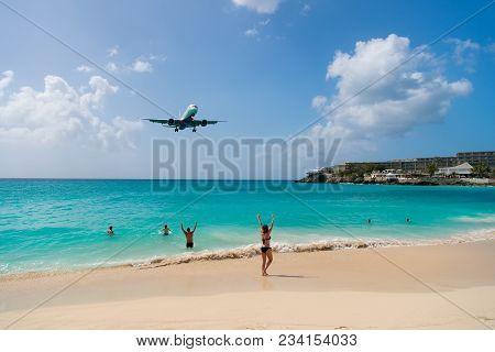 Plane Land Over People On Beach Of Philipsburg, Sint Maarten. Jet Flight Low Fly Over Blue Sea. Airp