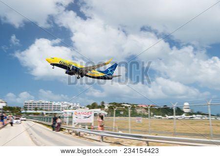 Philipsburg, Sint Maarten - February 13, 2016: Plane Low Fly Over Maho Beach. Jet Flight Land On Clo