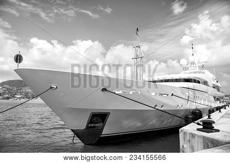 Yacht Luxury Boat At Pier In Philipsburg, St Maarten In Sea Or Ocean Water On Sunny Day On Cloudy Sk