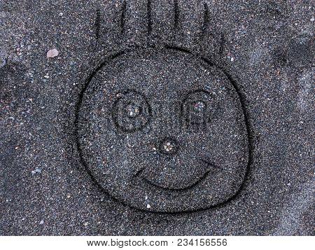 Handwritten Cute Baby Face On Sand Beach Background. Dark Sand Beach Smile Face Of Lovely Baby. Symb