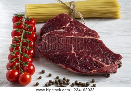 Raw Meat, Beef Steak, Brench Of Ripe Cherry Tomatoes, Spaghetti, Health Food, Top View. White Wooden