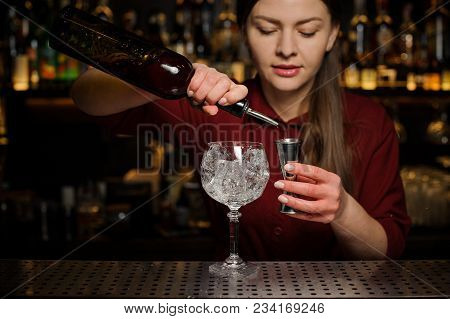 Barmaid The Blonde In A Red Dress Is Standing At The Bar And Pouring Red Wine Into A Glass, Preparin