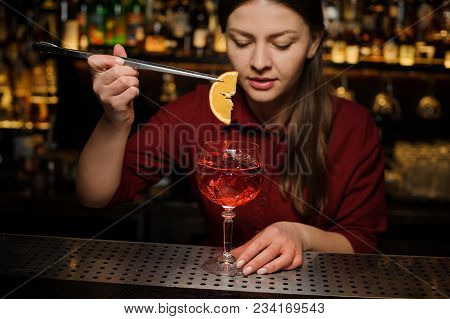 Barmaid In A Red Dress Finishes The Preparation Of An Alcohol Cocktail Spritz Veneziano, Adding A Sl