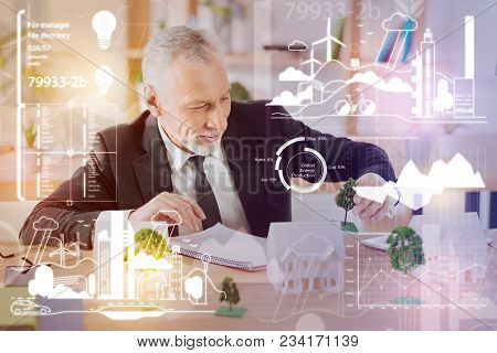 Miniature Tree. Cheerful Calm Attentive Architect Carefully Holding A Miniature Tree And Looking At