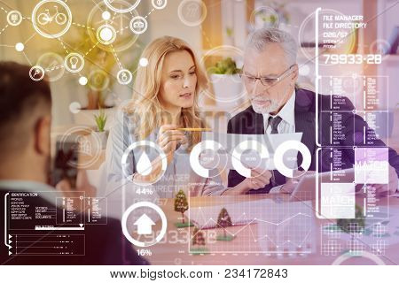 Reading statistics. Clever professional young secretary showing important documents to an experienced smart engineer and feeling confident poster