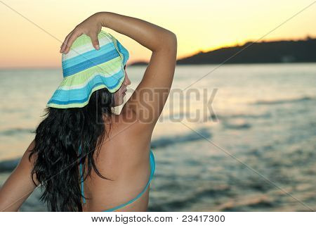 Woman With Hat Looking In Profile On Beach