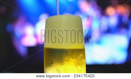 Beer Is Pouring From The Top Into A Pint Glass.