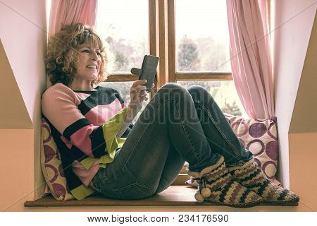 People, A Mature Woman Relaxing On A Window Seat With Pink Curtains And Cushions Looking At Mobile P