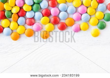 Colorful Round Candies On White Rustic Wooden Background  With Copy Space. Different Small Colored C