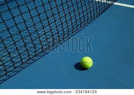 Yellow Tennis Ball Is Laying Near Black Net.