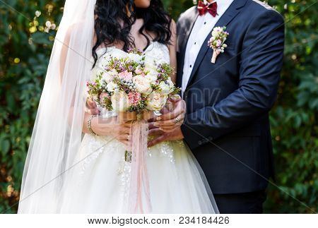 Beautiful Lush Bridal Bouquet With Lace Ribbons In Bride's Hand. Happy Bride And Groom Hugging After