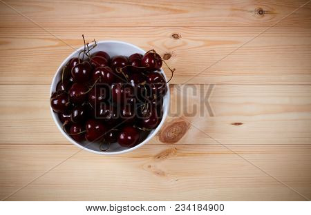 Red Ripe Cherries Berries In Bowl On  Wooden Background. Top View With Copy Space.