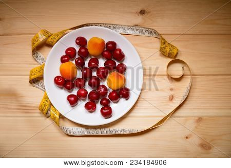 Fruits And Measuring Tape On Wooden Background. Top View. Weight Loss And Healthy Diet.