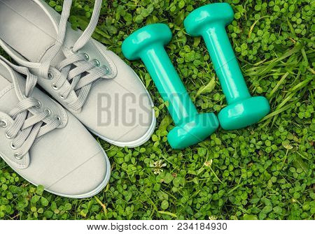 Sports Shoes And Dumbbells On Grass. Fitness Training In The Open Air.