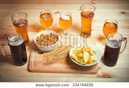 Beer Mugs, Glasses, Chips, Salted Straws And Pretzels  On Wooden Table. Selective Focus.
