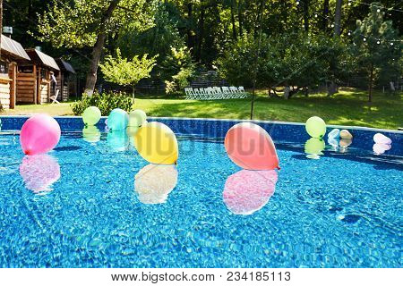 Swimming Pool With Colorful Balloons On Blue Water Outdoor, Copy Space. Poolside Party In Garden. Ai