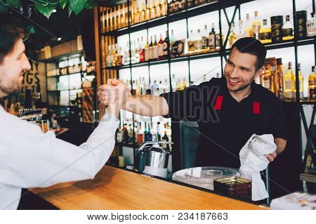 Cut View Of Barman Greeting His Friend And Shaking His Hand. He Is Happy To See His Friend. Everythi