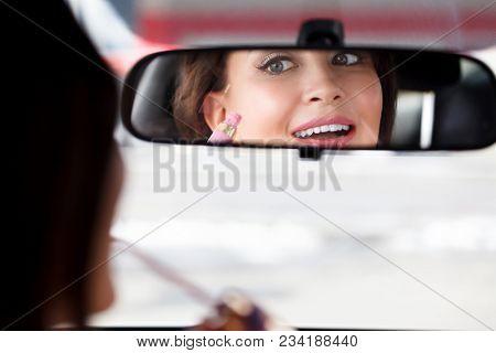 Pretty woman driver doing makeup