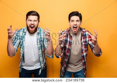 Portrait of a two angry young men shouting loud isolated over yellow background