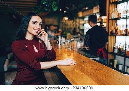 Attractive Brunete Girl Sitting In The Club Near Bar Stand And Talking On The Phone. She Is Smiling.