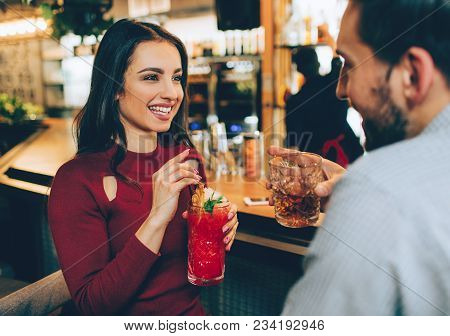 Beautiful Girl Sitting In The Club With Ac Guy. She Holds A Glass Of Cocktail In Her Hands. She Is L