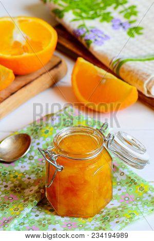 Homemade Citrus Jam. Sweet Orange Jam In A Glass Jar, Textile Napkin, Fresh Orange Slices On A Table