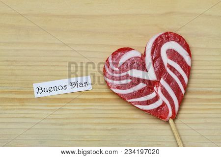 Buenos Dias (which Means Good Morning In Spanish) Card With Red And White Lollipop On Wooden Surface