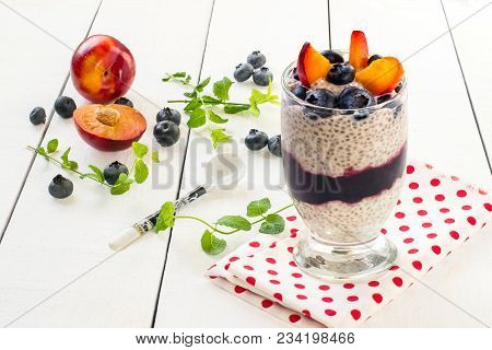 Chia Pudding With Yoghurt, Jam, Blueberries And Plums On White Wooden Background. Cleansing, Diet, H